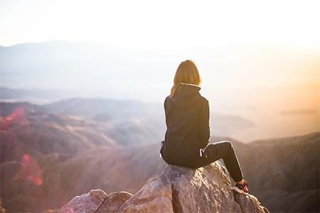 femme assise en haut d'une montagne avec une veste