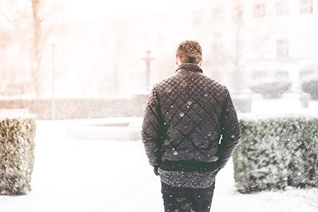 homme qui marche dans la neige avec un blouson chauffant